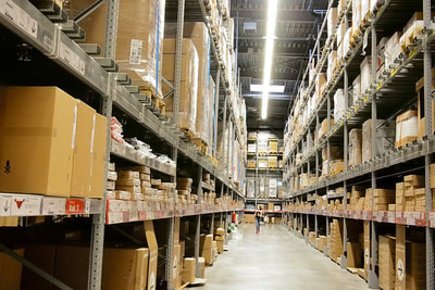 A shipping & receiving clerk searching for product and checking inventory in a warehouse